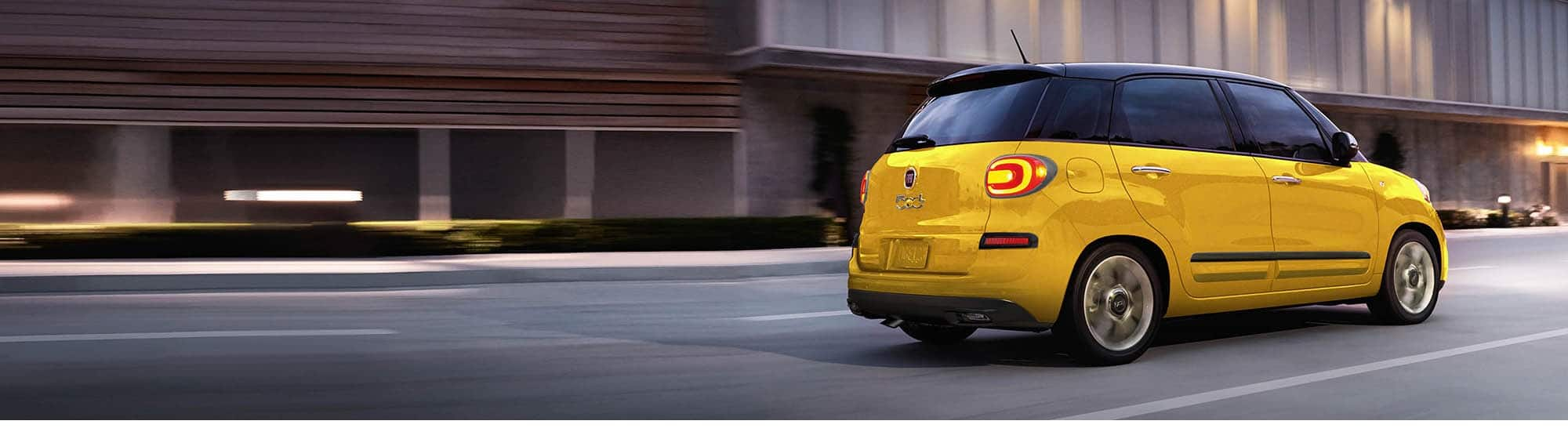 A rear profile view of a 2020 Fiat 500L Trekking being driven on a city street.
