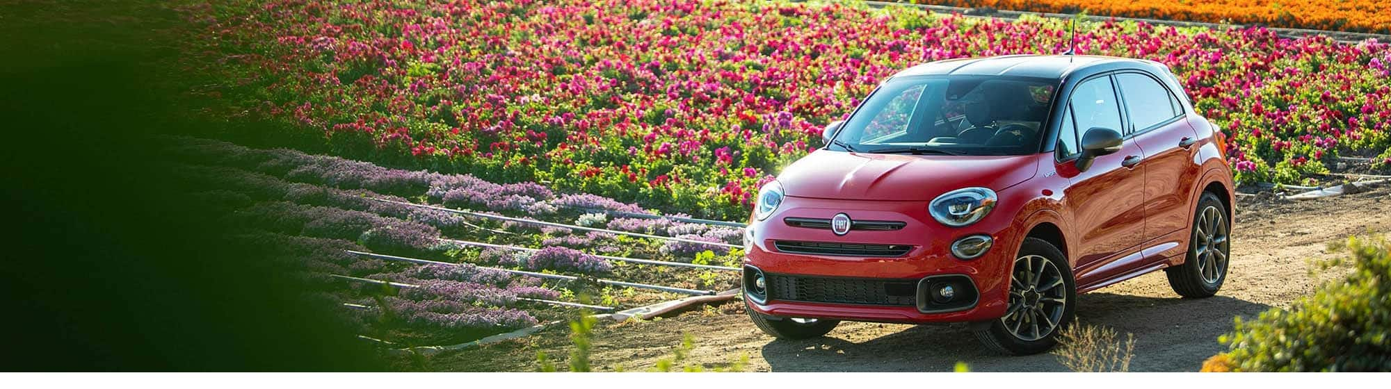 A red 2020 Fiat 500X Sport on a dirt road beside a field of flowers.
