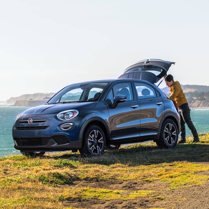 Fiat 500X parked near a waterfront with a man opening the rear hatch open.