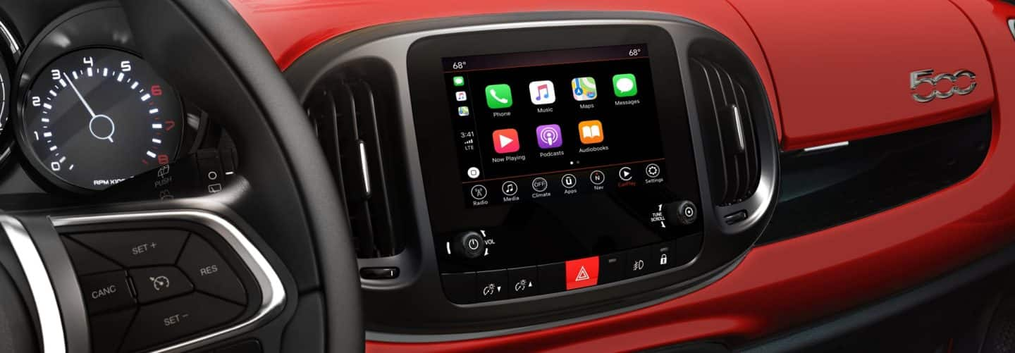 A close-up of the steering wheel and touchscreen in the 2020 FIAT 500L, with Apple CarPlay icons displayed on the touchscreen.
