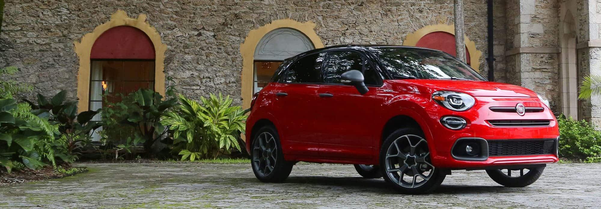 Vista de lateral de medio perfil de un Fiat 500X 2020 rojo estacionado sobre una calle de adoquines.