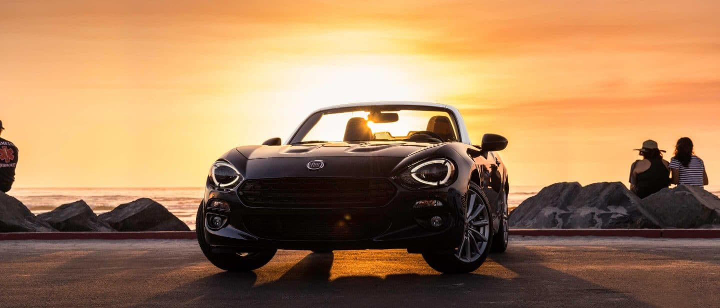 A front view of the 2020 Fiat 124 Spider parked on a beach at sunset. In the background two people are facing the water.
