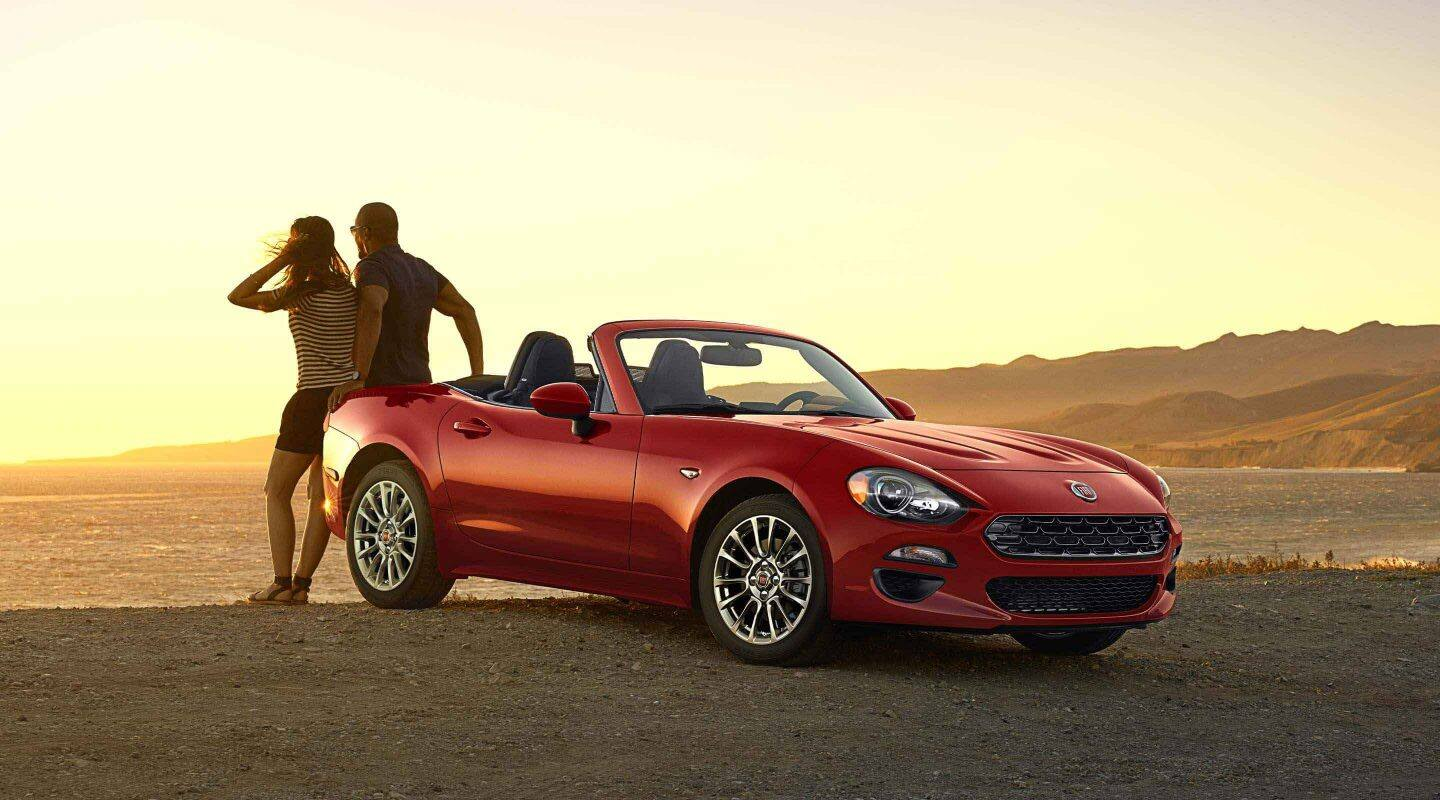 Display A three-quarter side view of the 2020 Fiat 124 Spider Classica parked near the water with a couple looking out at the sunset.