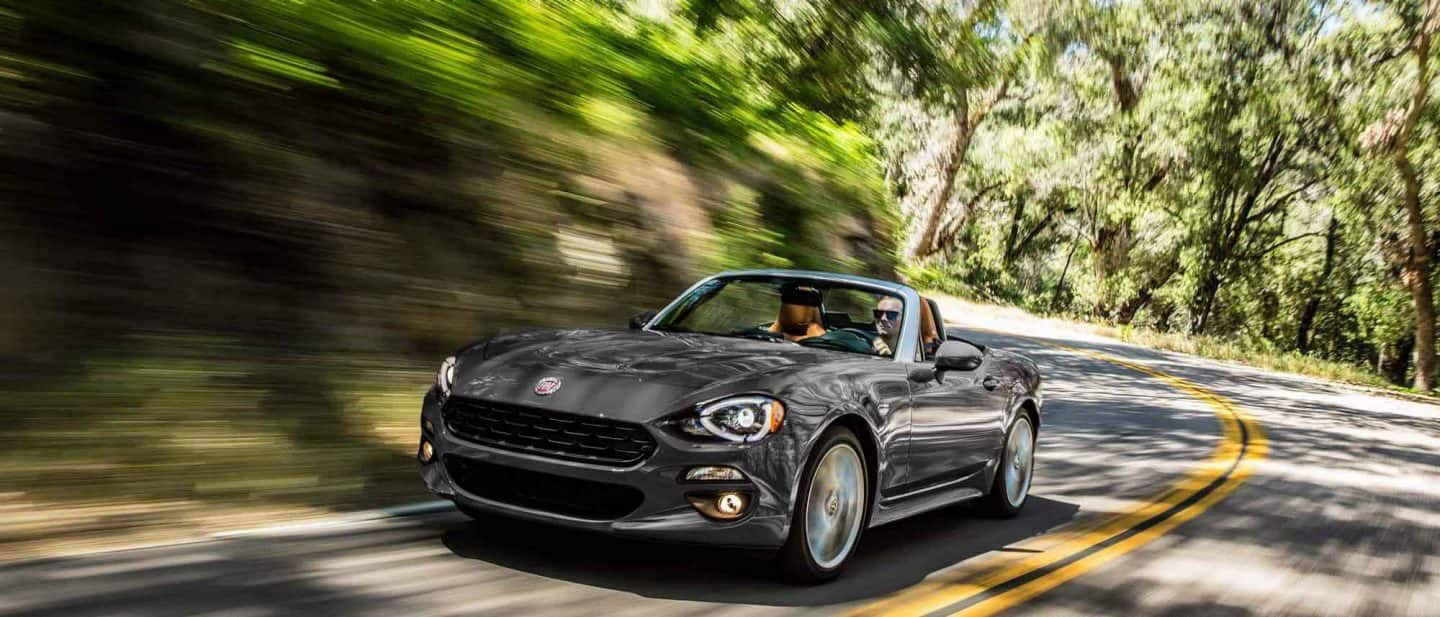 A front three-quarter view of the 2020 Fiat 124 Spider with its top down being driven on a curve in a wooded area.