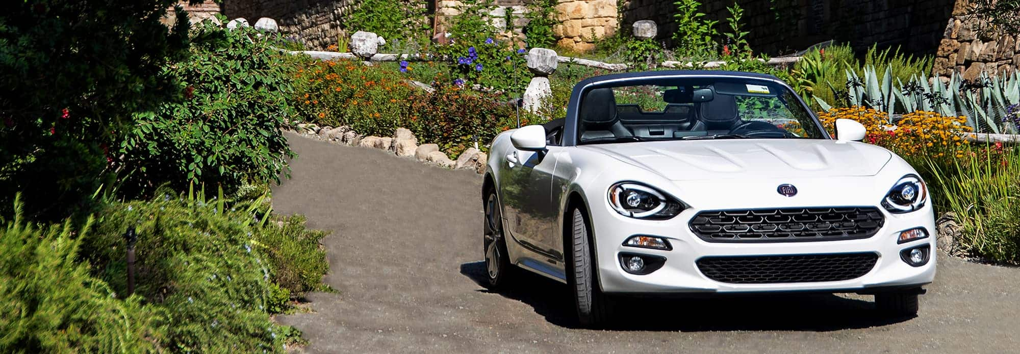 A front view of a white 2020 Fiat 124 Spider Lusso parked in a garden full of various plants and shrubs.