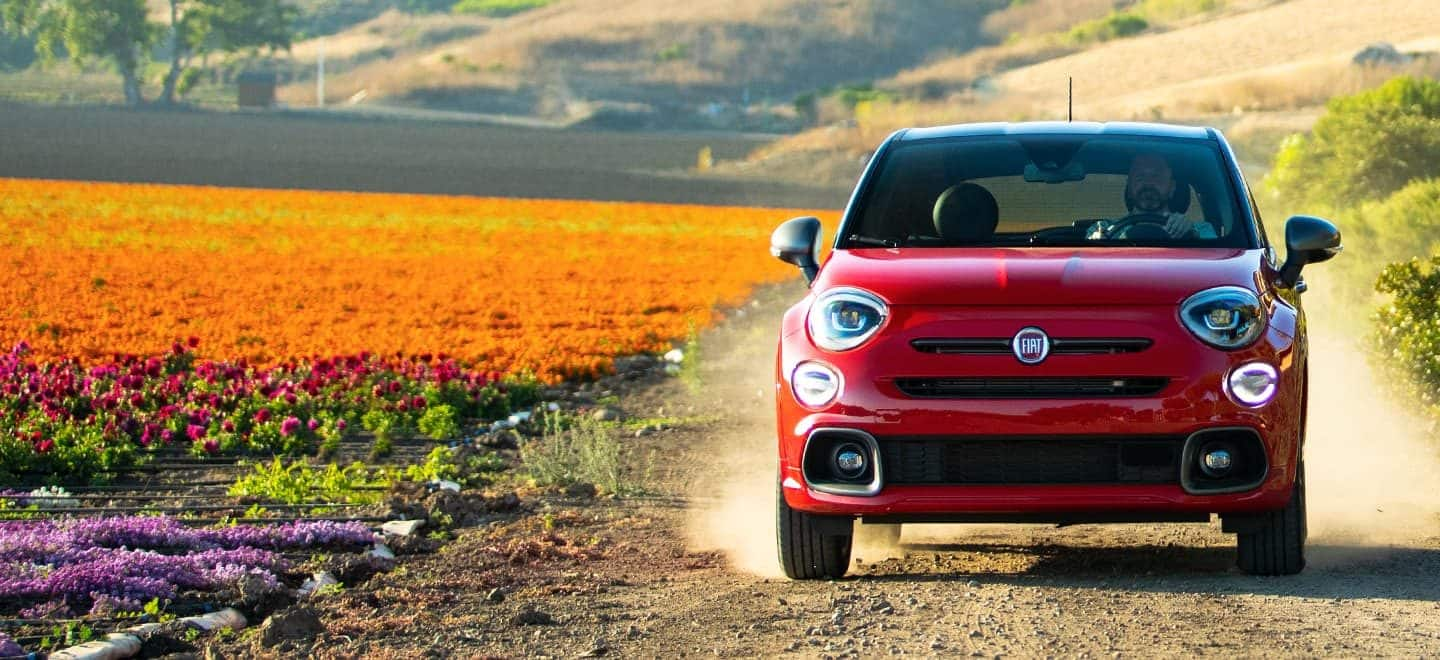 Display A head-on view of the 2021 Fiat 500X Sport with the available Sport Discount Package, being driven beside a field of flowers.