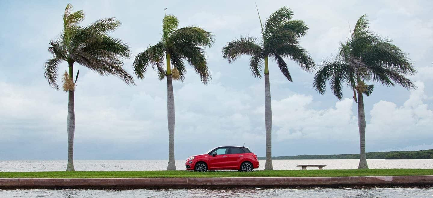 Display A profile view of the 2021 Fiat 500X Sport parked next to the beach with four palm trees towering overhead.