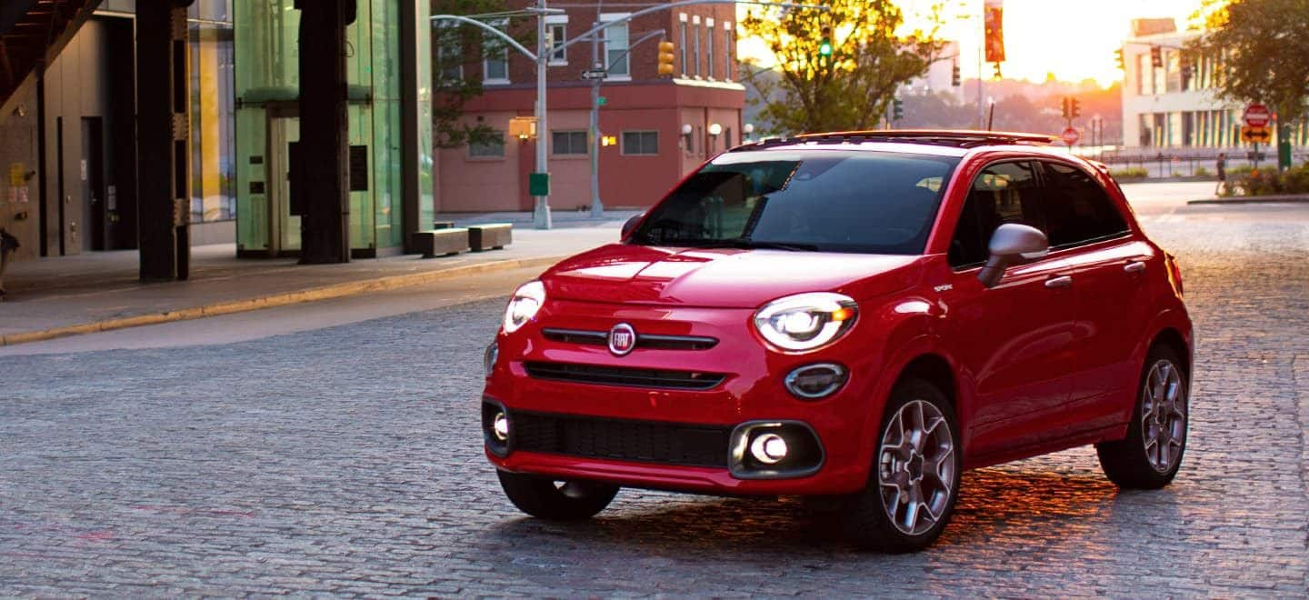 Display The 2021 Fiat 500X Sport with the available Sport Discount Package, parked on a cobblestone street near an intersection.