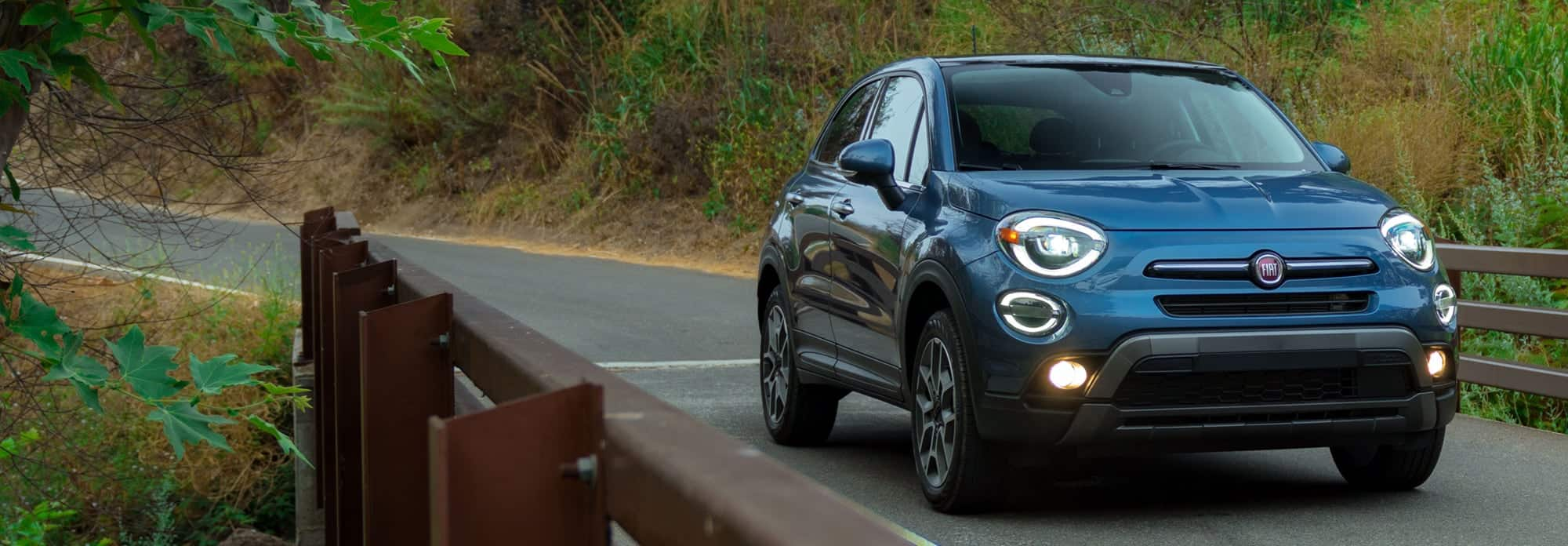 A blue 2020 Fiat 500X Trekking Plus parked on a bridge in the woods at dusk.