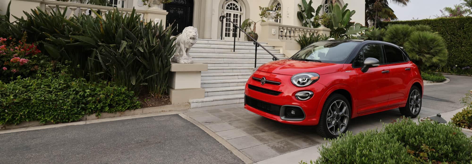 Vista delantera de medio perfil del FIAT 500X Sport 2021 rojo estacionado junto a una casa opulenta.