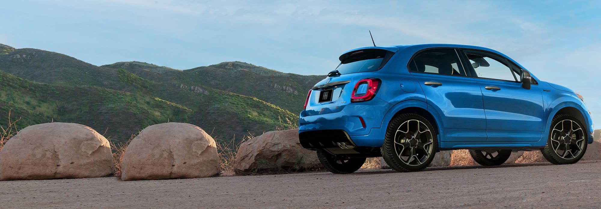 Vista delantera de medio perfil de unFiat500X Sport2021 azul estacionado en un costado, con montañas de fondo.