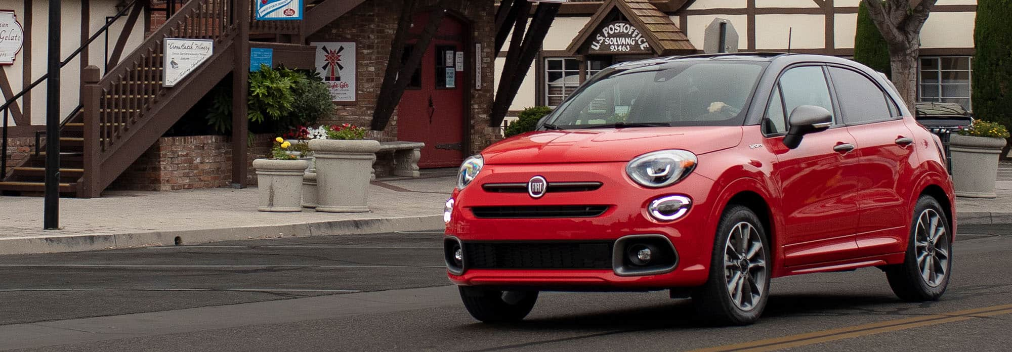 Vista delantera de medio perfil del Fiat 500X Sport 2021 rojo andando por una calle de ciudad frente a una oficina postal.