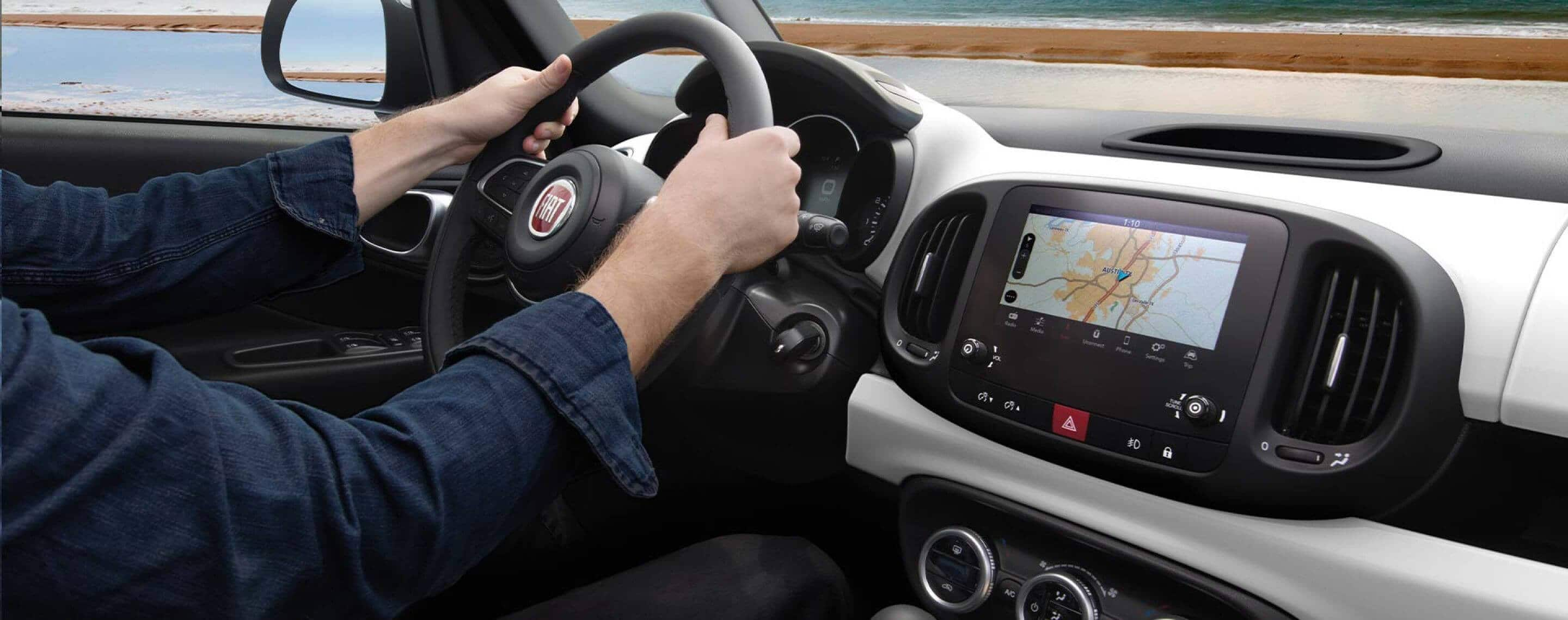 A driver with his hands on the wheel of a 2020 Fiat 500L Trekking as the Uconnect touchscreen navigation system displays a route map.